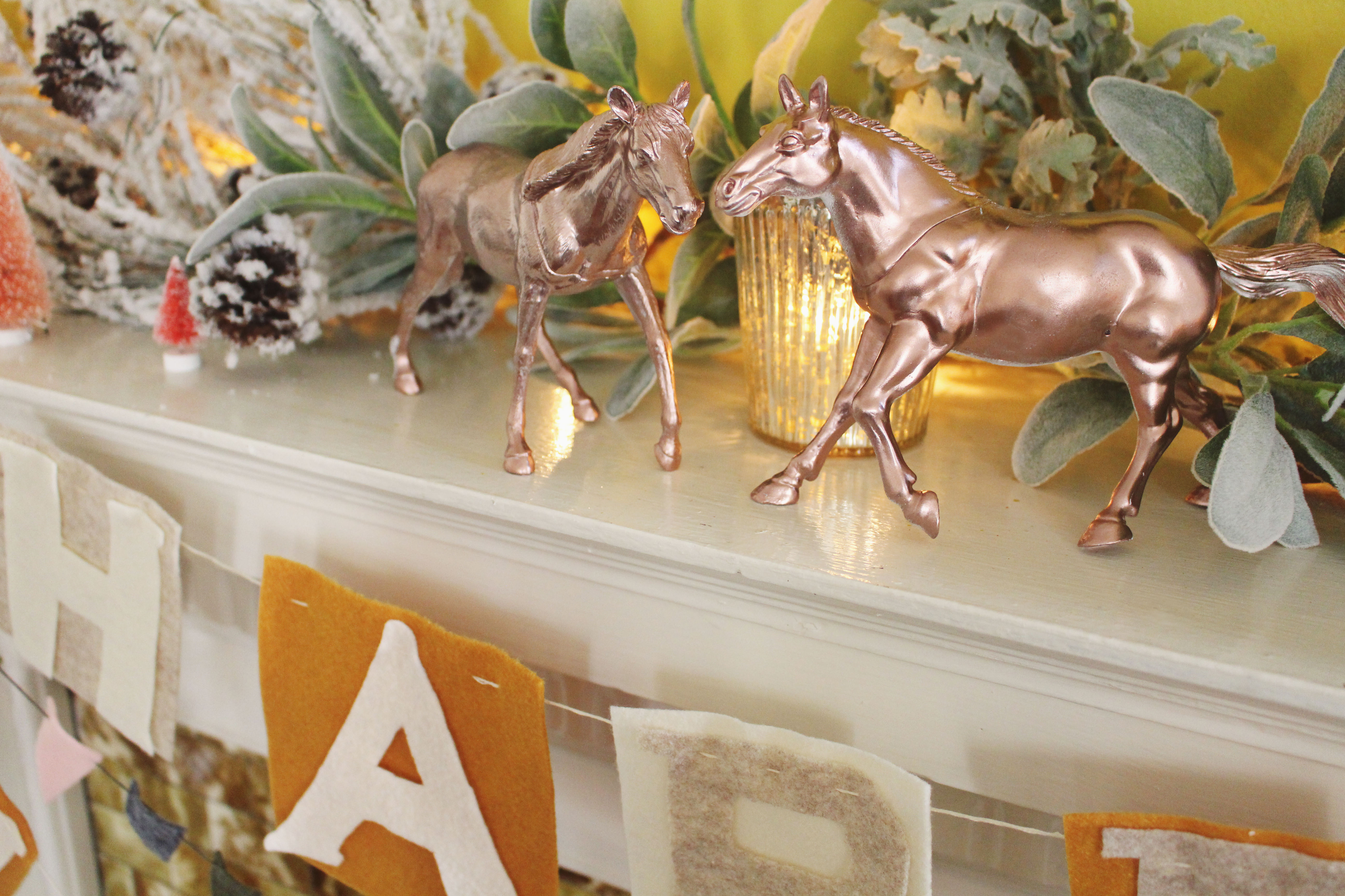 DIY rose gold horses are an unexpected holiday mantle detail