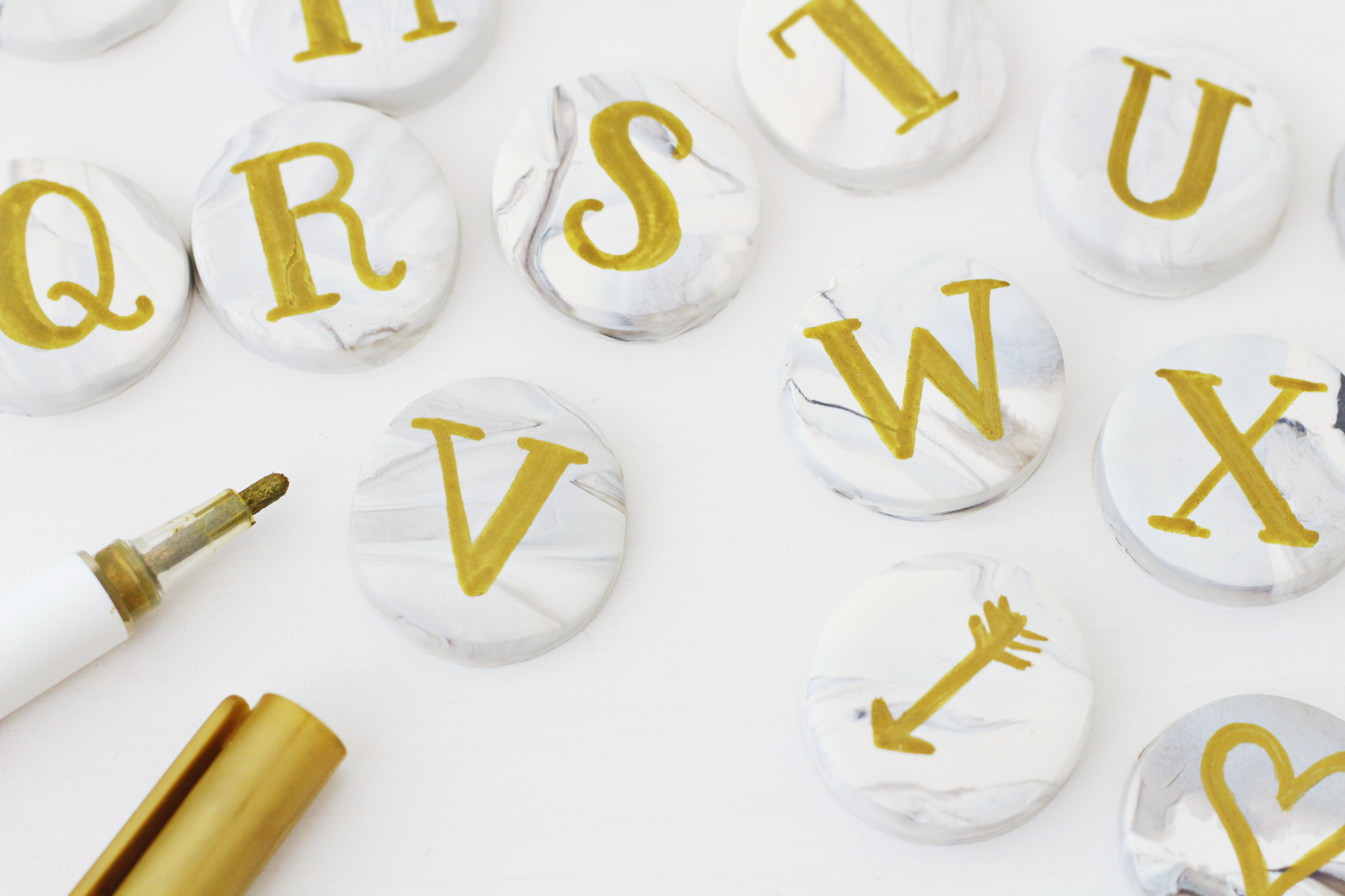 Use a gold paint pent to hand letter your marble clay magnets