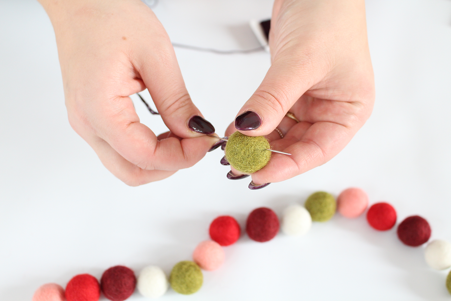String felt balls onto embroidery floss for an easy DIY felt garland